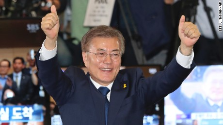 South Korea's presidential candidate Moon Jae-in of the Democratic Party raises his hands as his party leaders, members and supporters watch on television local media's results of exit polls for the presidential election at National Assembly in Seoul, South Korea, Tuesday, May 9, 2017. Exit polls forecast that liberal candidate Moon win the election Tuesday to succeed ousted President Park Geun-hye. (AP Photo/Lee Jin-man)