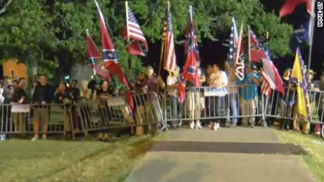 Those opposed to the Davis monument's removal wave Confederate and US flags Thursday morning.
