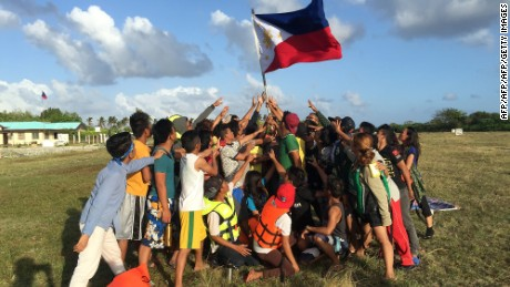 Filipino children hold up a national flag during a 2015 protest on Pagasa island against Beijing's claims in the South China Sea.