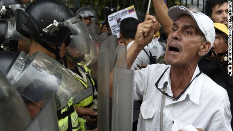 "Opposition activists confront riot police during the so-called ""march of the grand-parents"" protest against the government in Caracas on May 12, 2017. Daily clashes between demonstrators -who blame elected President Nicolas Maduro for an economic crisis that has caused food shortage- and security forces have left 38 people dead since April 1. Protesters demand early elections, accusing Maduro of repressing protesters and trying to install a dictatorship.  / AFP PHOTO / JUAN BARRETO        (Photo credit should read JUAN BARRETO/AFP/Getty Images)"