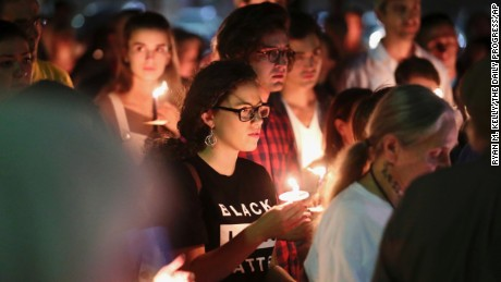 People who support removal of the monuments hold candles during a counterprotest on Sunday.