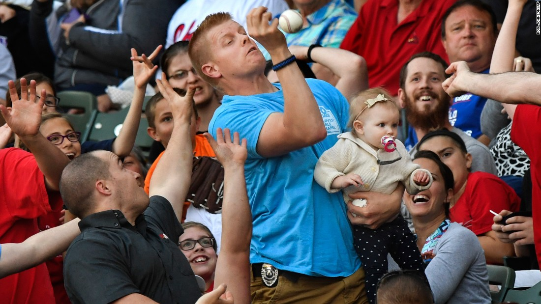 Mark Ehlke holds his 1-year-old daughter, Elsie, while catching a foul ball during a minor-league game in Peoria, Illinois, on Friday, May 12.