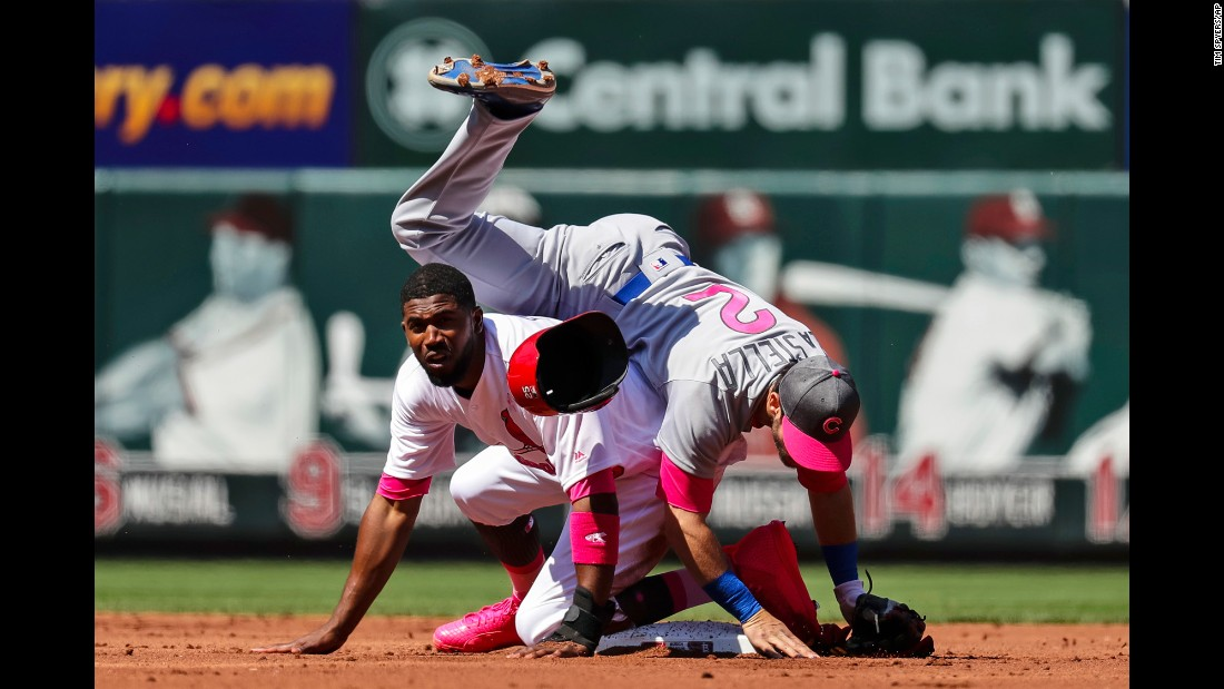Tommy La Stella, an infielder for the Chicago Cubs, falls over St. Louis' Dexter Fowler after turning a double play on Saturday, May 13. Major League Baseball teams were wearing pink for Mother's Day.
