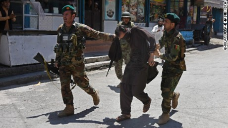 Afghan soldiers capture a suspect after Wednesday's attack on a TV station in Jalalabad, Afghanistan.