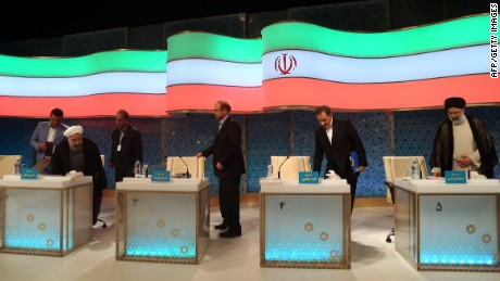 Rouhani (L) and Raisi (R) take their seats for a televised debate in late April.