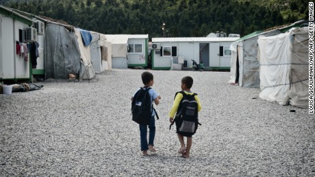 Children walk with their schoolbags on May 11, 2017 at Malakasa refugee camp, some 50km north of Athens, where around 700 refugees, mainly from Afghanistan, wait their fate. Life is at a standstill for Afghan refugees in Greece who are not relocalizable in Europe, not knowing  what the future holds for them and lacking support for Greek language and culture learning. / AFP PHOTO / LOUISA GOULIAMAKI        (Photo credit should read LOUISA GOULIAMAKI/AFP/Getty Images)