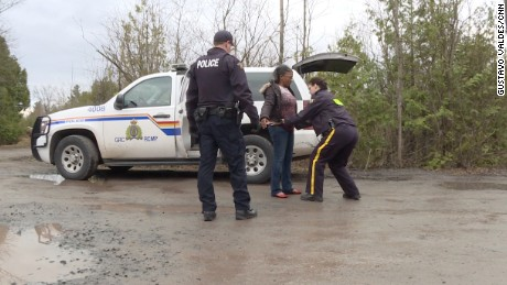 Canadian police detain a Haitian immigrant who just crossed the border.