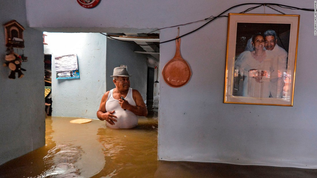 A man wades through his flooded home in Cali, Colombia, on Tuesday, May 16. Heavy rains cause the overflowing of the Cauca River.