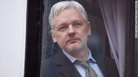 "WikiLeaks founder Julian Assange is seen through the window of the door leading to the balcony of the Ecuadorian embassy in central London on February 5, 2016 from where he addressed the media. During a press conference on February 5 Julian Assange, speaking via video-link, called for Britain and Sweden to ""implement"" a UN panel finding saying that he should be able to walk free from Ecuador's embassy, where he has lived in self-imposed confinement since 2012. / AFP / BEN STANSALL        (Photo credit should read BEN STANSALL/AFP/Getty Images)"