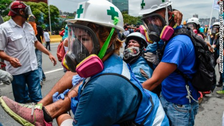 TOPSHOT - An opposition demonstrator wounded during clashes with riot police is carried away by medics during a protest against Venezuelan President Nicolas Maduro, in Caracas on May 3, 2017. Venezuela's angry opposition rallied Wednesday vowing huge street protests against President Nicolas Maduro's plan to rewrite the constitution and accusing him of dodging elections to cling to power despite deadly unrest. / AFP PHOTO / JUAN BARRETO        (Photo credit should read JUAN BARRETO/AFP/Getty Images)