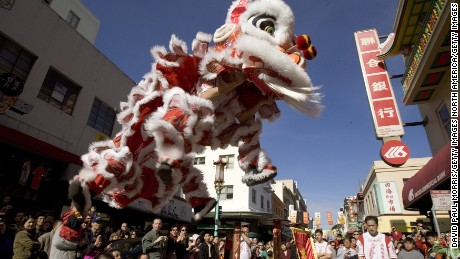 SAN FRANCISCO - JANUARY 29:  People watch a traditional lion dance in front of a bank on the first day of Chinese New Year on January 29, 2006 in Chinatown, San Francisco, California. The Lunar New Year celebration, which ushered in the Year of the Dog at midnight will last  for 3 days bringing families together to share food and pray at temples for good health and prosperity in the coming year. (Photo by David Paul Morris/Getty Images)