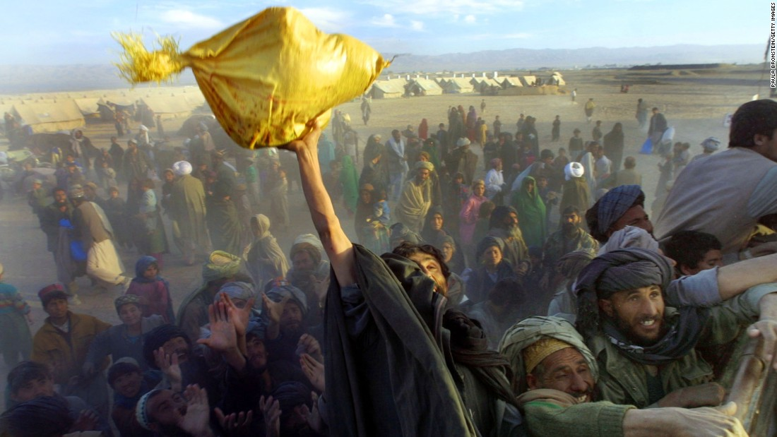 Afghan refugees reach for bags of rice and sugar being handed out by a local aid organization near Chaman, Pakistan, on December 4, 2001. Tens of thousands of Afghans had crossed the border since the 9/11 attacks.