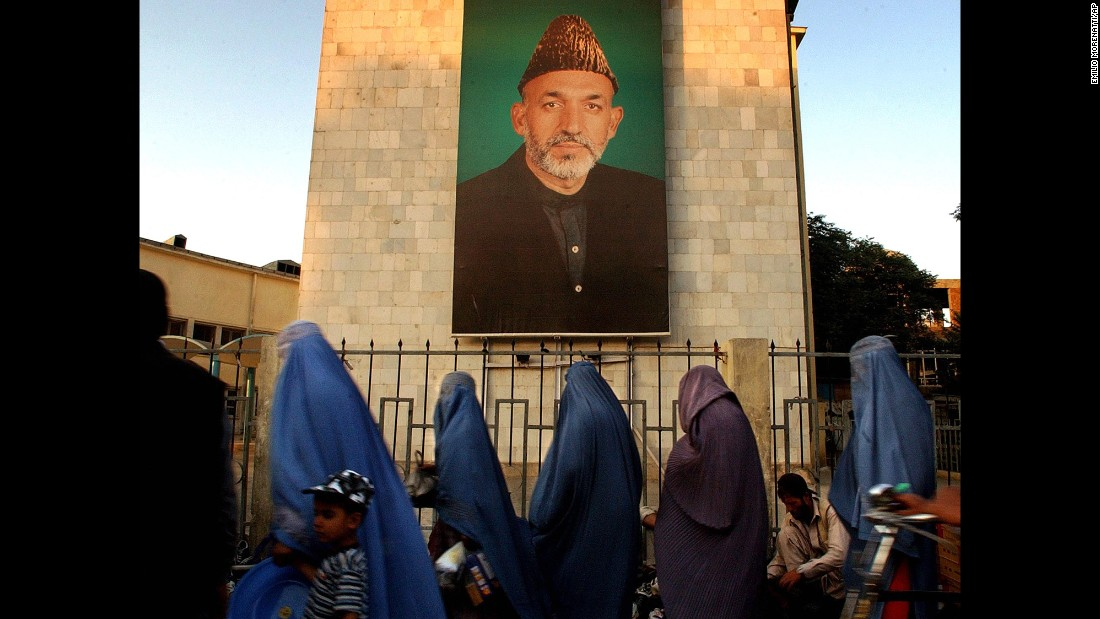 Afghan women walk past a portrait of Karzai in Kabul on October 26, 2004. Karzai had been in a leadership role since December 2001, when an interim government was formed after the Taliban lost its last major stronghold.