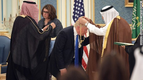 US President Donald Trump (C) receives the Order of Abdulaziz al-Saud medal from Saudi Arabia's King Salman bin Abdulaziz al-Saud (R) at the Saudi Royal Court in Riyadh on May 20, 2017.