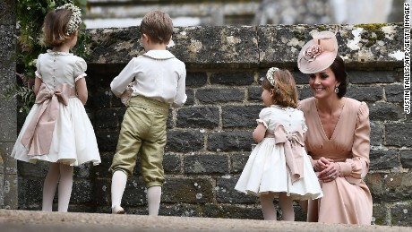 Catherine, Duchess of Cambridge stands with her daughter Britain's princess Charlotte, a flower girl, following the wedding of her sister Pippa Middleton to James Matthews.