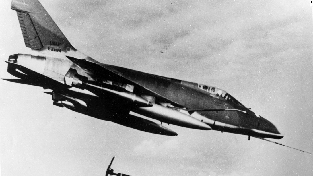 Made by North American Aviation and designed to reach maximum speeds exceeding 925 mph, the F-100 was the first USAF fighter that could fly faster than the speed of sound during level flight. This D model of the F-100 is shown dropping a Snake-Eye bomb on a suspected Viet Cong position in 1966.