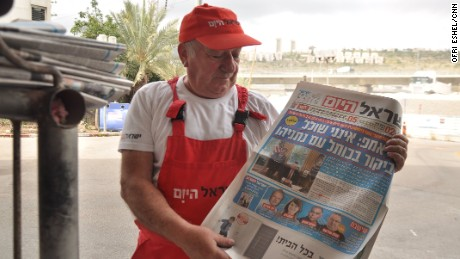 A man sells newspapers at Haifa bus station.
