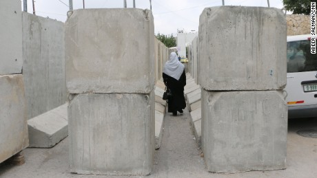 A Palestinian woman crosses through the wall at the Bethlehem checkpoint.