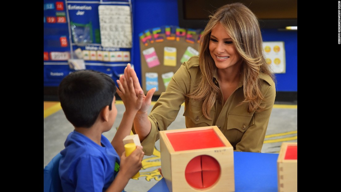 The first lady high-fives a child during a visit to the American International School in Riyadh, Saudi Arabia, on Sunday, May 21.