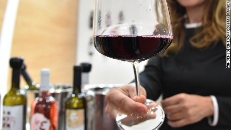 "A woman hands a glass of wine from the ""Le Moire"" wine maker of the Italian Calabria region on April 10, 2016 during the 50th edition of the Vinitaly wine exhibition in Verona.  Vinitaly is the worlds largest wine event, hosting  more than 4164 exhibitors, looking to promote a vast range of rich and exotic varieties of wines, spirits and other alcoholic beverages.  / AFP / VINCENZO PINTO        (Photo credit should read VINCENZO PINTO/AFP/Getty Images)"