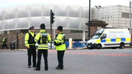 MANCHESTER, ENGLAND - MAY 23: Police officers stand at the Miller Street and Corporation Street Crossroads, in front of  the Manchester Arena on May 23, 2017 in Manchester, England.  An explosion occurred at Manchester Arena as concert goers were leaving the venue after Ariana Grande had performed.  Greater Manchester Police have confirmed 19 fatalities and at least 50 injured. (Photo by Dave Thompson/Getty Images)