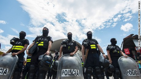 Costa Rican police personnel in riot gear form a line in the border with Panama, 320 km south of San Jose on April 14, 2016.  Police was deployed after more than 1,000 migrants, most of them Cubans, thronged and then stormed across Panama's border into Costa Rica Wednesday in a desperate bid to reach the United States. / AFP / Ezequiel Becerra        (Photo credit should read EZEQUIEL BECERRA/AFP/Getty Images)