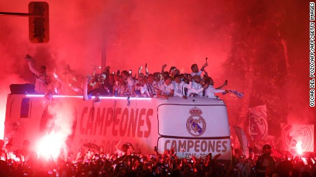 TOPSHOT - Real Madrid football team fans surround the bus as Real Madrid players celebrate the team's win on Plaza Cibeles in Madrid on May 22, 2017 after the Spanish league football match Malaga CF vs Real Madrid CF held at La Rosaleda stadium in Malaga on May 21, 2017. Madrid sealed a first La Liga title in five years on Sunday -- and 33rd in total -- with a 2-0 victory at Malaga to bring a halt to Barcelona's domination of domestic matters having won six of the previous eight titles.   / AFP PHOTO / OSCAR DEL POZO        (Photo credit should read OSCAR DEL POZO/AFP/Getty Images)