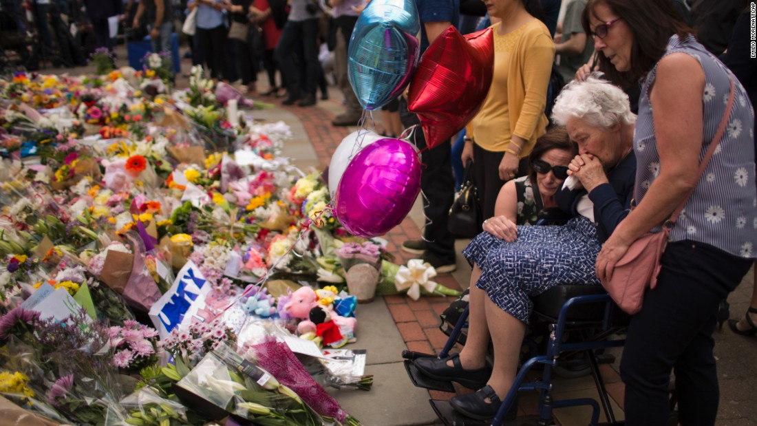 Women cry after placing flowers in Manchester on May 24.