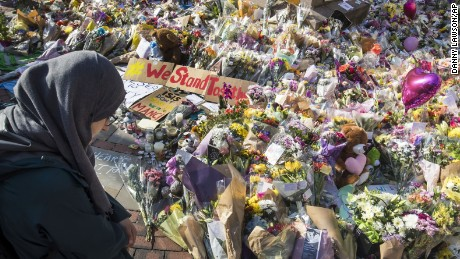A woman looks at the floral tributes and messages left for the victims of the concert blast, during a vigil at St Ann's Square in central Manchester, England.