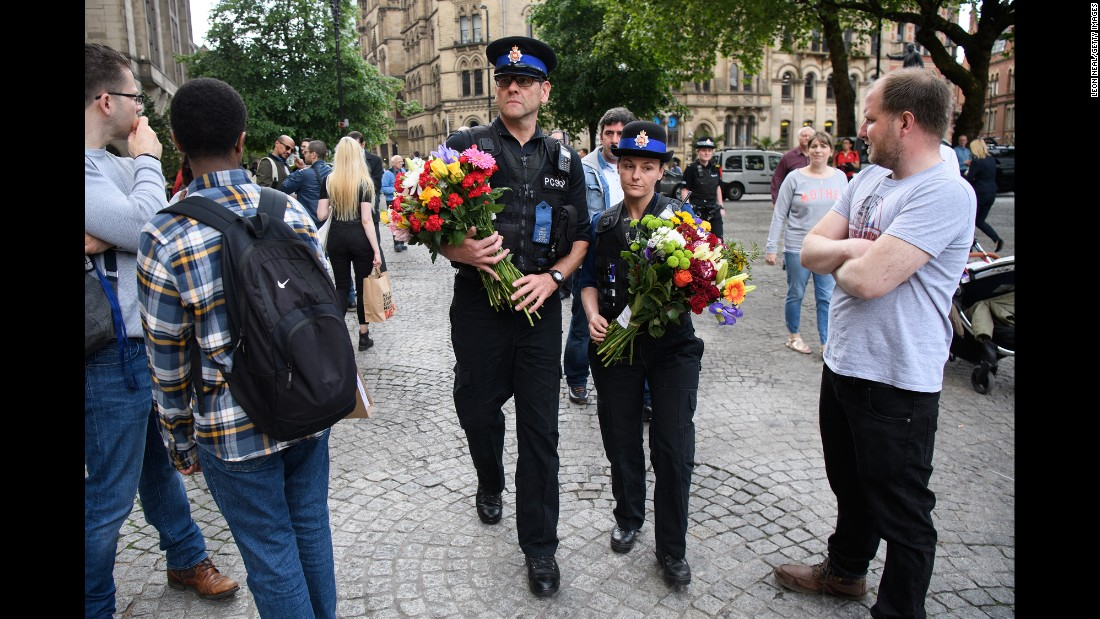 Police officers deliver flowers to a makeshift memorial in Manchester on Wednesday, May 24.