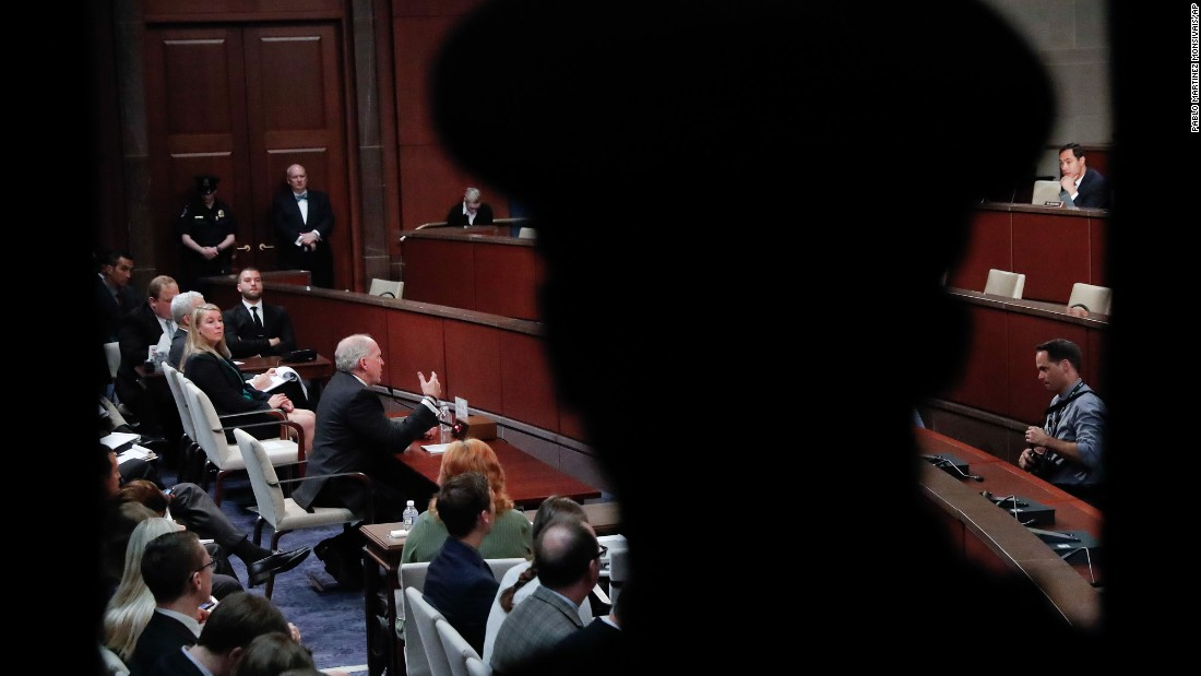 "A police officer, foreground, watches former CIA Director John Brennan<a href=""http://www.cnn.com/2017/05/23/politics/john-brennan-house-intelligence-committee/"" target=""_blank""> testify in Washington</a> on Tuesday, May 23. Brennan told House investigators that Russia ""brazenly interfered"" in US elections, including actively contacting members of Donald Trump's campaign. But he stopped shy of dubbing it ""collusion."""