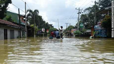 Sri Lankan residents travel by boat through floodwaters in the suburb of Kaduwela in the capital Colombo.