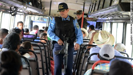 Honduran policemen check the passengers of a bus in the Marcala municipality, department of La Paz, 90 km west of Tegucigalpa, in the border with El Salvador, on November 30, 2016 . Honduran, Guatemalan and Salvadorean army troops are conducting a joint operation against drug trafficking and maras juvenile gangs activity.  / AFP / ORLANDO SIERRA        (Photo credit should read ORLANDO SIERRA/AFP/Getty Images)