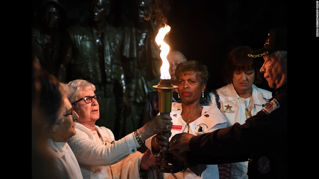 Gold Star Mothers and their supporters hold a torch as they recite the names of their fallen children during a candlelight vigil in Washington on Friday, May 26.