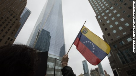 A demonstrator holds a Venezuelan flag during a protest outside of the Goldman Sachs Group Inc. headquarters in New York, U.S., on Tuesday, May 30, 2017. Goldman faces a probe by Venezuela's opposition leaders after buying bonds issued in 2014 by the state oil company, a purchase some lawmakers said bolsters President Nicolas Maduro as he grapples with accusations of human-rights violations. Photographer: Alexander F. Yuan/Bloomberg via Getty Images