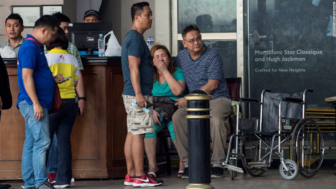 Relatives of a victim sit in front of the Resorts World Hotel, a popular tourist site in Manila, the capital of the Philippines that was on lockdown after a shooting on June 2, 2017. A police official said the incident was a robbery attempt by one person and not a terrorist attack.