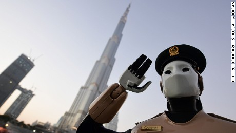 The world's first operational police robot stands at attention as they prepare a military cannon to fire to mark sunset and the end of the fasting day for Muslims observing Ramadan, in Downtown Dubai on May 31, 2017. / AFP PHOTO / GIUSEPPE CACACE        (Photo credit should read GIUSEPPE CACACE/AFP/Getty Images)