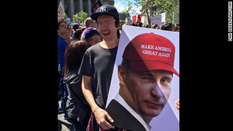 "Jake Rowland holds a sign with an image of Russian President Vladimir Putin wearing a Trump campaign ""Make America Great Again"" cap at New York protest."