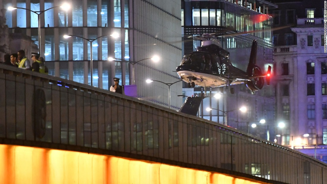 A helicopter flies near London Bridge.