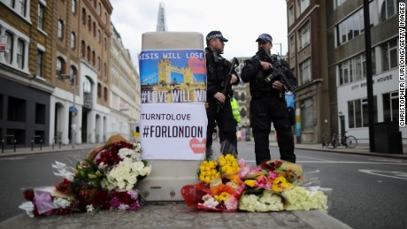 Armed police stand guard in front of floral tributes on Southwark Street near the scene of the attack.