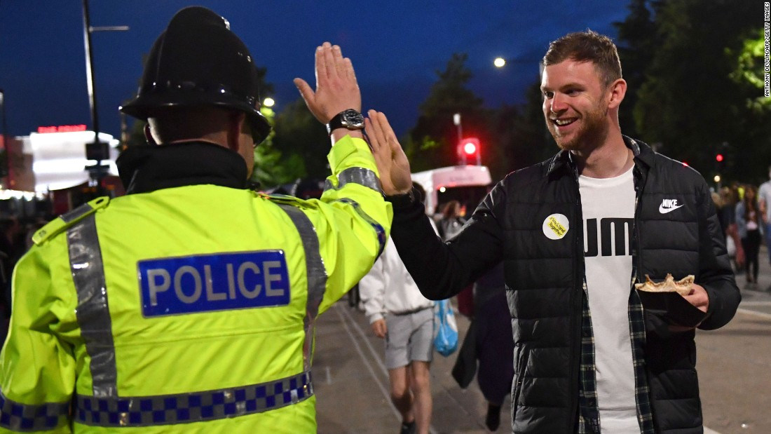 A fan high-fives a police officer as fans leave the concert.