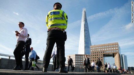 Commuters walk past a police officer on London Bridge in London, Monday, June 5.