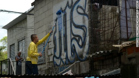 Parolees paint over graffiti associated with the Mara Salvatrucha's gang in San Salvador, during an operation to take back gang-controlled neighborhoods, on August 16, 2016.  The Salvatrucha (MS-13) and 18th Street gangs are the main cause of the violence escalation plaguing El Salvador, where an estimated 60,000 people belong to gangs, 15,000 of them in prison. / AFP / Marvin RECINOS        (Photo credit should read MARVIN RECINOS/AFP/Getty Images)