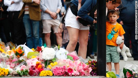A woman comforts a child after laying flowers at a pedestrian crossing on the south side of London Bridge, close to Borough Market in London on June 5, 2017, in tribute to the victims of the June 3 attacks.