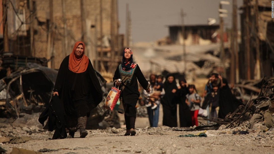 "Iraqi civilians escape the fierce battle raging in the Zinjili neighborhood in western Mosul on June 4, 2017. As these women passed by Iraqi security forces, the woman in the orange hijab screamed, ""Where were you for the last three years?"""
