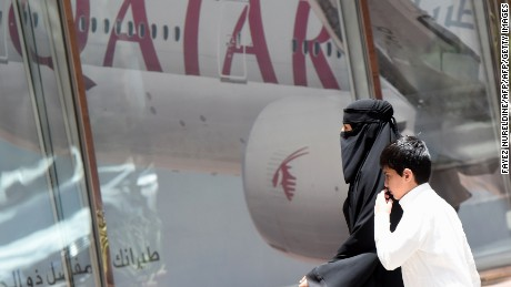 A picture taken on June 5, 2017 shows a Saudi woman and a boy walking past the Qatar Airways branch in the Saudi capital Riyadh, after it had suspended all flights to Saudi Arabia following a severing of relations between major gulf states and gas-rich Qatar. Arab nations including Saudi Arabia and Egypt cut ties with Qatar accusing it of supporting extremism, in the biggest diplomatic crisis to hit the region in years. / AFP PHOTO / FAYEZ NURELDINE        (Photo credit should read FAYEZ NURELDINE/AFP/Getty Images)