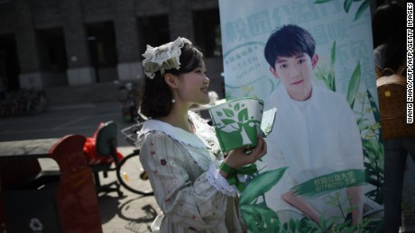 A woman hands out leaflets during an event for fans of TFBoys in April 2017. Another band member Wang Yuan is on the background poster.