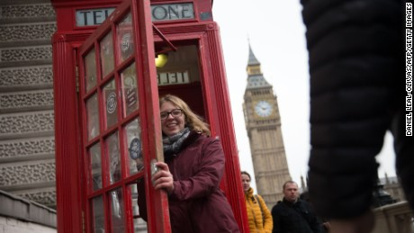 A woman poses for a photograph as she leaves a red public telephone box in Westminster, central London on January 16, 2017. Prime Minister Theresa May won endorsement from US President-elect Donald Trump over her Brexit course but sterling plunged on Monday on fears that Britain could be on a collision course with its EU allies. / AFP / Daniel LEAL-OLIVAS        (Photo credit should read DANIEL LEAL-OLIVAS/AFP/Getty Images)