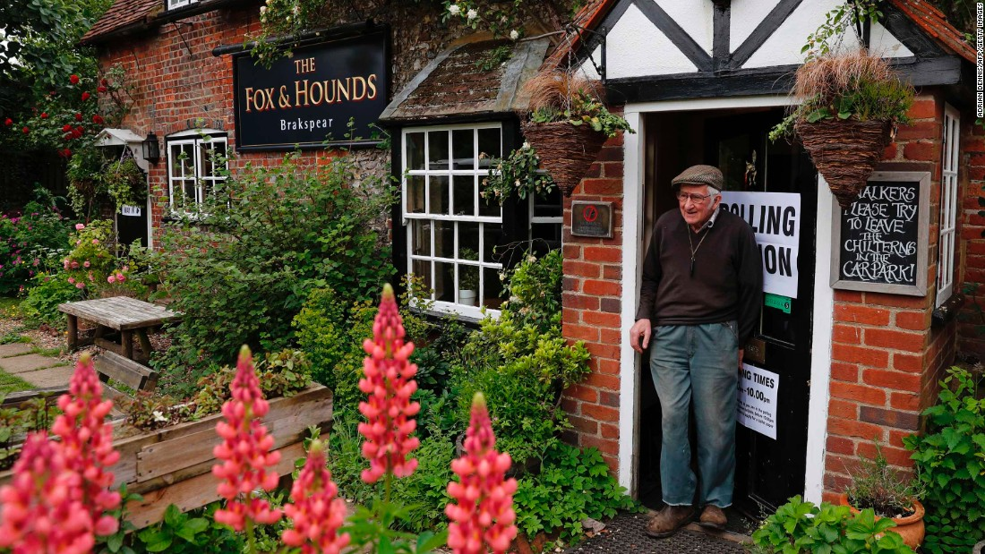 A man leaves a polling station at a pub in Christmas Common, near Oxford, England.
