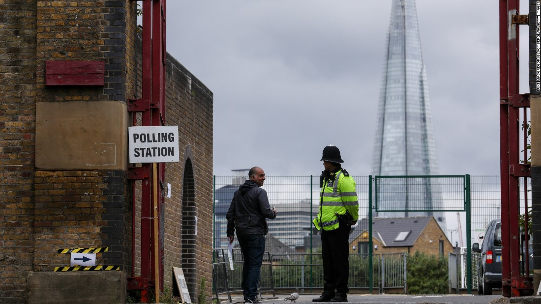 A voter greets a police officer at a polling station in London.